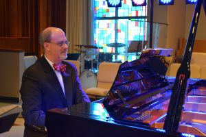 Dr. Gilliland playing piano in a suit 3