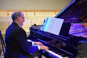 Dr. Gilliland playing piano in a suit 6