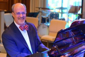 Dr. Gilliland playing piano in a suit 2