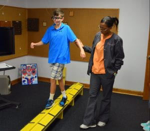Boy with prism glasses walking on a balance beam in vision therapy